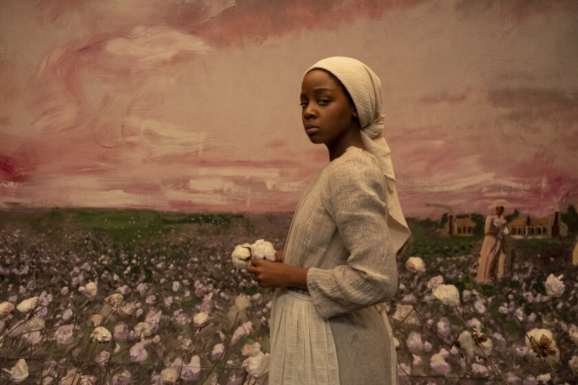 A young enslaved woman stands before a painting of a cotton field