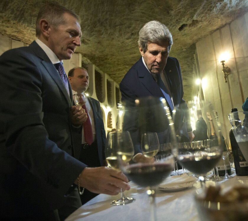 Secretary of State John Kerry picks up a glass of wine as he tours the Cricova Winery and cellars, Wednesday, Dec. 4, 2013, in Chisinau, Moldova. Created in 1952, Cricova is probably the best-known name in wine in Moldova. The state-run winery includes an astonishing underground tunnel system for wine storage, a labyrinth of galleries running for 120km (about 75 miles). (AP Photo/Pablo Martinez Monsivais, Pool)