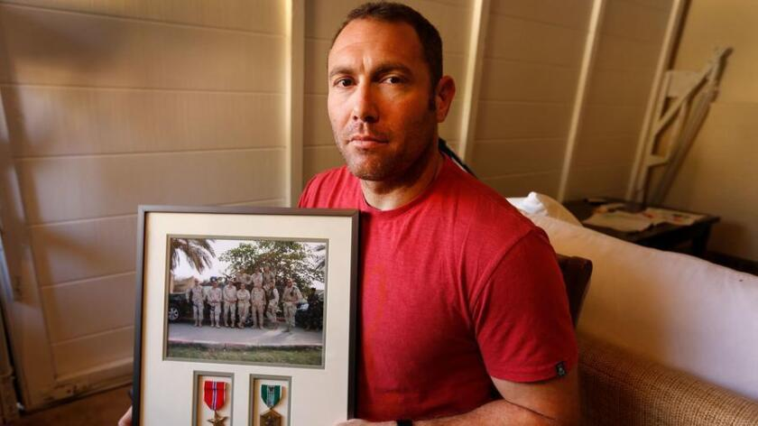 Robert D'Andrea, a retired Army major who lives in Los Angeles, holds a photo of his team on his first deployment to Iraq. Nearly 10,000 California National Guard soldiers have been ordered to repay huge enlistment bonuses a decade later.