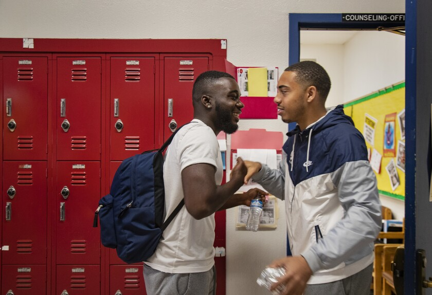LOS ANGELES, CA - MARCH 7, 2019: Senior Damion Lester, Jr., left, greets a former classmate as he