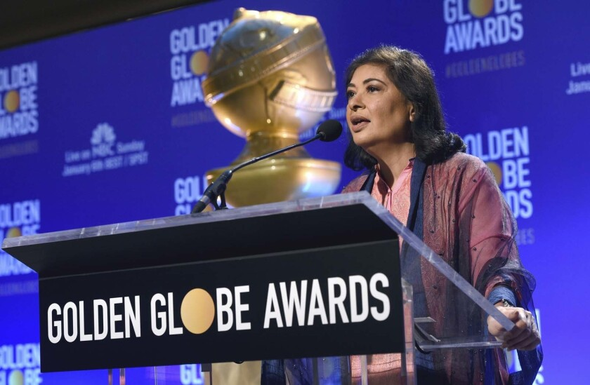 Meher Tatna at a lectern with a large Golden Globe award in the foreground.