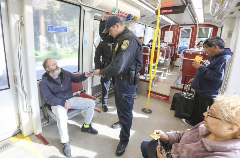 Transit officer Marc Vargas, who does code compliance enforcement for the San Diego Metropolitan Transit System, checks trolley riders for valid fares on the Green Line on January 9, 2020.