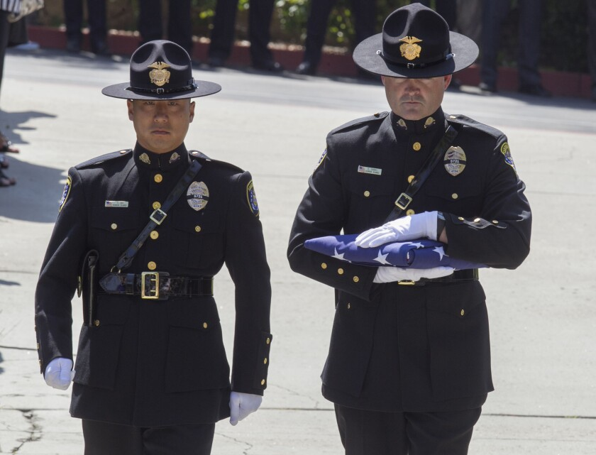 Two members of the SDPD Honor Guard carried ina U.S. flag before the service.