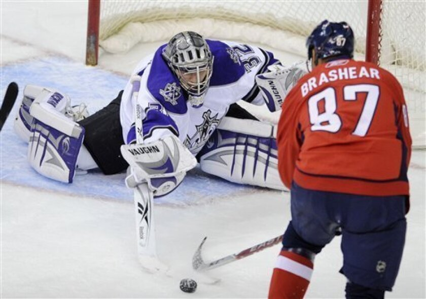 Los Angeles Kings goalie Jonathan Quick (32) reaches out for the puck against Washington Capitals' Donald Brashear (87) during the second period of an NHL hockey game, Thursday, Feb. 5, 2009, in Washington.(AP Photo/Nick Wass)