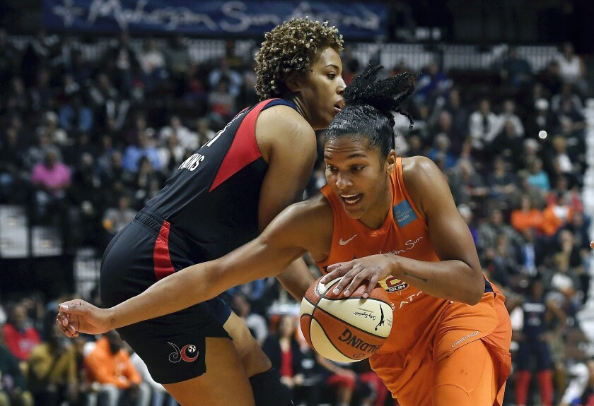 Connecticut Sun's Alyssa Thomas, front, drives past Washington Mystics' Tianna Hawkins during the first half in Game 4 of the WNBA Finals on Tuesday in Uncasville, Conn.