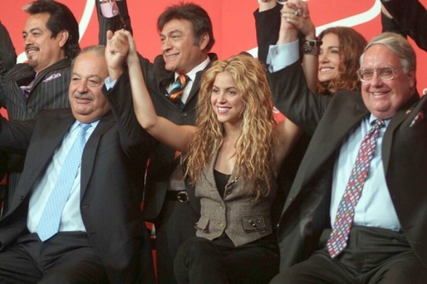 SOLIDARITY: Carlos Slim Helú (front, from left), Shakira and Howard Graham Buffett raise their interlocked hands to support early childhood development funding in Latin America.