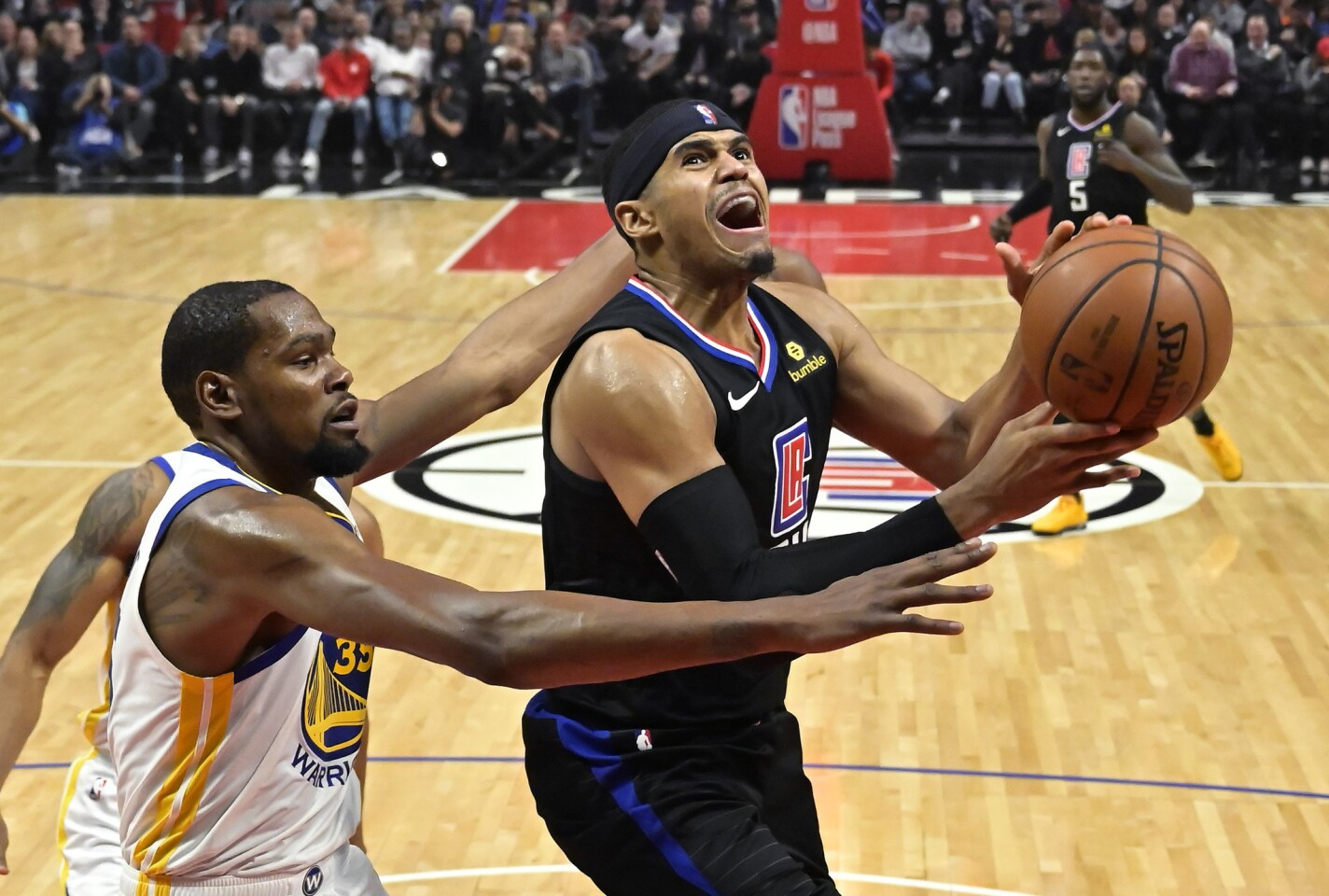 Los Angeles Clippers forward Tobias Harris, right, shoots as Golden State Warriors forward Kevin Durant defends during the second half of an NBA basketball game Friday, Jan. 18, 2019, in Los Angeles. The Warriors won 112-94. (AP Photo/Mark J. Terrill)