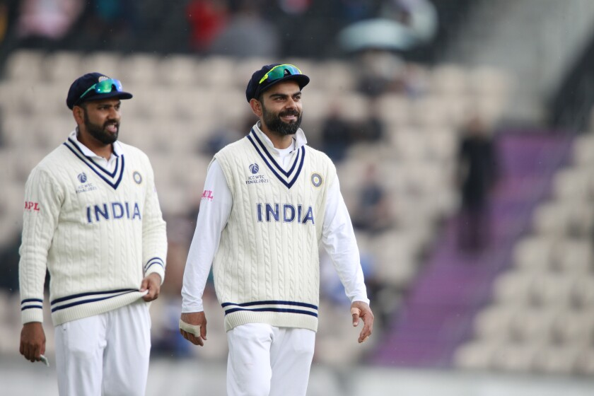 India's captain Virat Kohli, right, stands with teammate Rohit Sharma during the third day of the World Test Championship final cricket match between New Zealand and India, at the Rose Bowl in Southampton, England, Sunday, June 20, 2021. (AP Photo/Ian Walton)