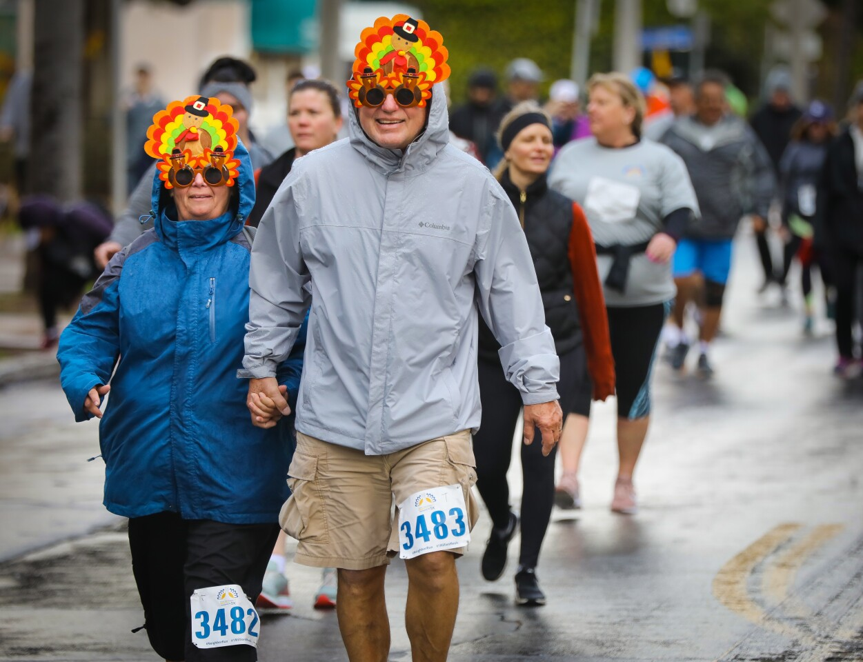 Sporadic rain showers didn't stop Carla Scott, left, and her husband Doug Scott, right, who were two of the thousands who participated in the 18th annual Father Joe's Villages Thanksgiving Day 5K in Balboa Park, November 28, 2019, in San Diego, California. The money raised helps support homeless efforts in San Diego. Although thousands participated, because of the rain, about 1,000 less ran and walked this year according to Deacon Jim Vargas, president and CEO of Father Joe's Villages.