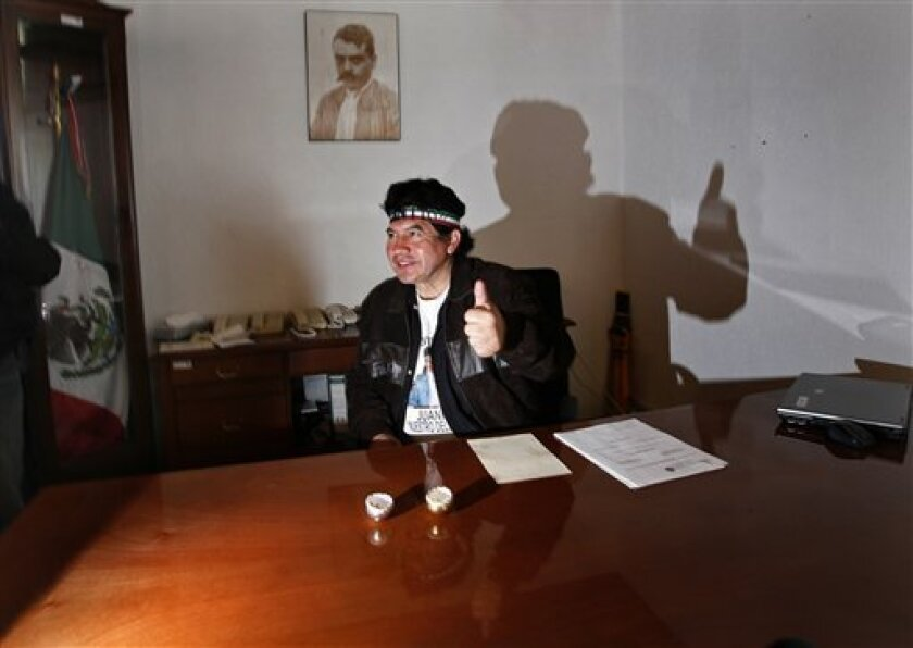 "Rafael Acosta gives a thumbs up to the press as he sits in the offices of the borough chief of Ixtapalapa in Mexico City, Monday, Nov. 30, 2009.  Acosta, better known for his nickname ""Juanito"" and his Rambo-style headband, has taken over the offices of Mexico City's most populous borough and says"