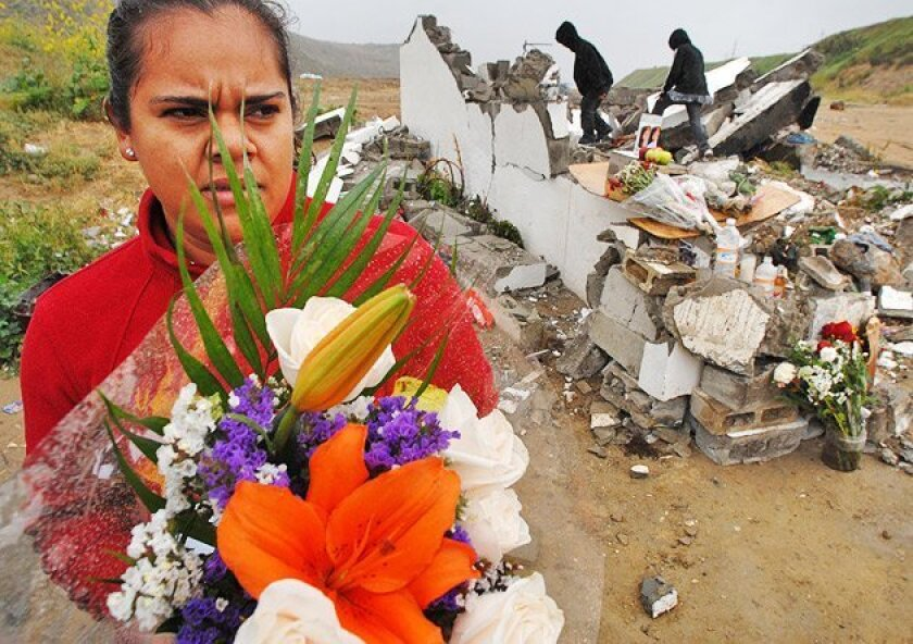 Indolesa Beltran delivered an offering at the rubble of a shrine to La Santa Muerte destroyed last weekend outside Tijuana. (David Maung)