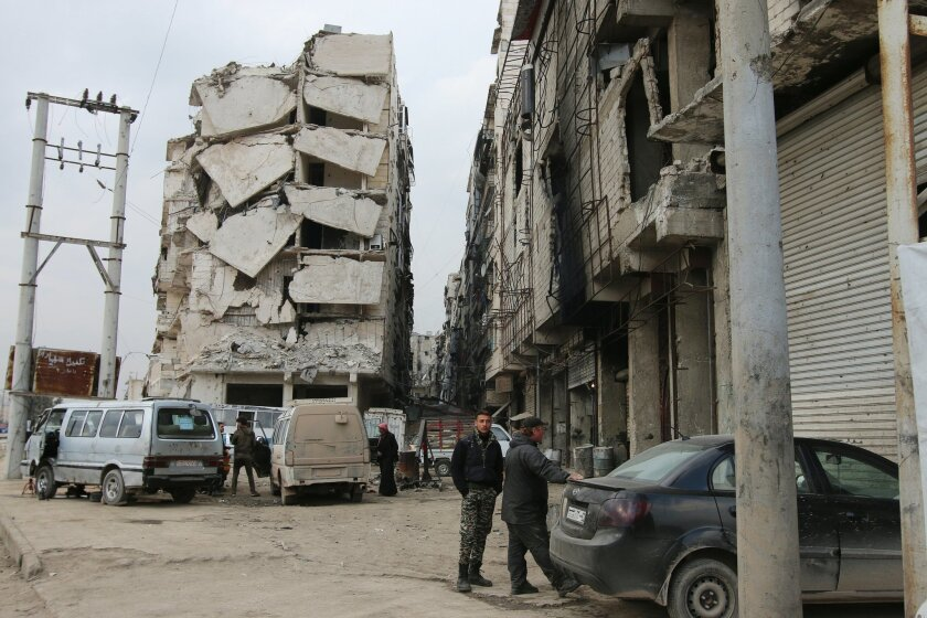 In this Thursday, Feb. 11, 2016 photo, a building is seen with heavy damage in Aleppo, Syria. The fighting around Syria's largest city of Aleppo has brought government forces closer to the Turkish border than at any point in recent years, routing rebels from key areas and creating a humanitarian di