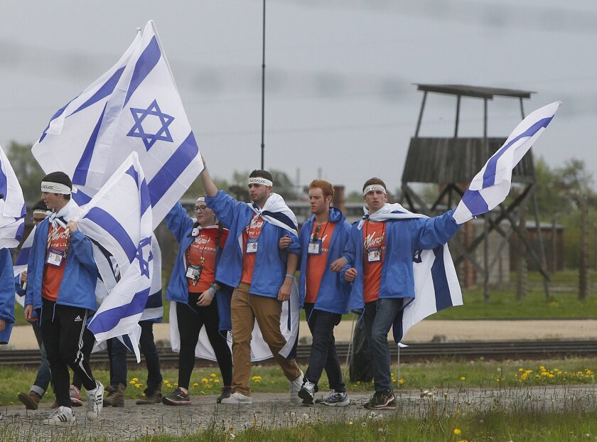 Young jewish people from Israel and other countries march in silence between the two parts of Auschwitz-Birkenau, the Nazi German death camp, in an annual march of the living in Oswiecim, Poland, on Monday, April 28, 2014, which is held in memory of some 6 million Jews killed during the Holocaust. This year, the march honors some 430,000 Hungarian Jews killed in Birkenau gas chambers in 1944. (AP Photo/Czarek Sokolowski)