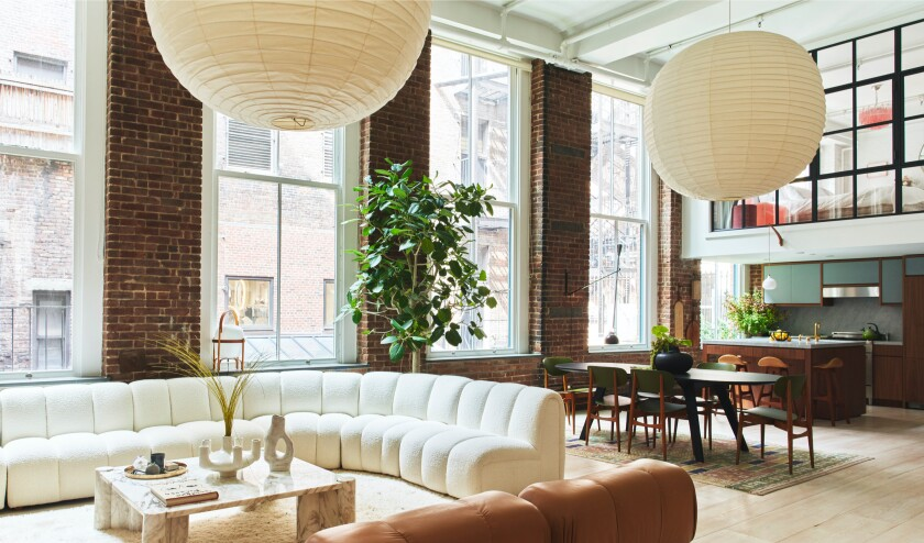 The two-bedroom home features exposed brick walls, original Corinthian columns and a lofted primary suite.