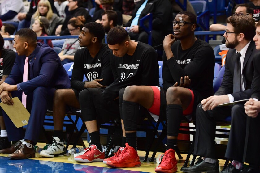SDSU's Montaque Gill-Caesar (23), Nolan Narain and center Valentine Izundu on the bench as the Aztecs lose at Air Force on Tuesday night.