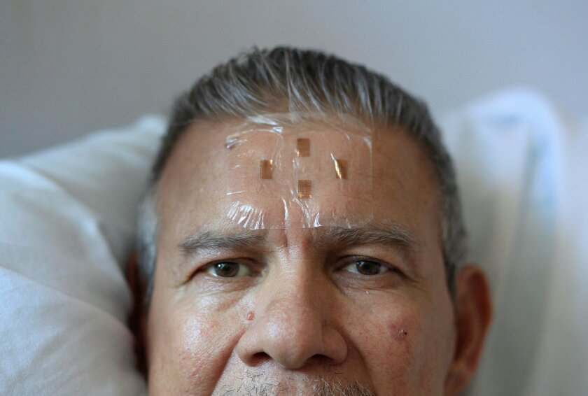 UC San Diego researcher Todd Coleman developed a flexible electronic biosensor that was recently placed on Alfonso Polanco, a 62 year-old patient at Thornton Hospital in La Jolla. The experimental biosensor is able to monitor electrical activity in the brain, helping doctors and nurses to monitor p