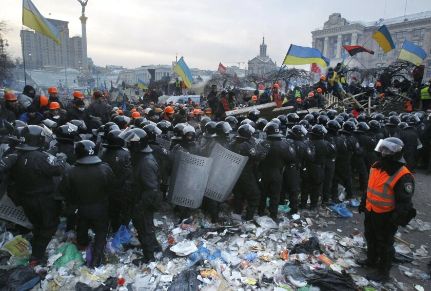 Pro-European Union activists wave flags as riot police pull back from Independence Square in Kiev, Ukraine, Wednesday, Dec. 11, 2013. Security forces clashed with protesters as they began tearing down opposition barricades and tents set up in the center of the Ukrainian capital early Wednesday, in an escalation of the weeks-long standoff threatening the leadership of President Viktor Yanukovych. (AP Photo/Sergei Grits)