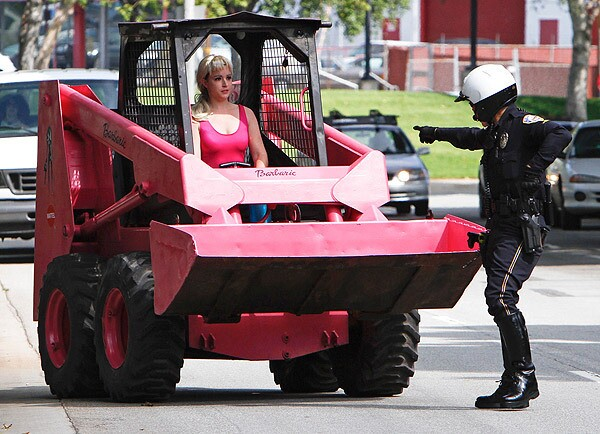 Elise Nabors, wearing a Barbie outfit and driving a pink skip loader, is stopped by a police officer near Mattel's headquarters in El Segundo during a protest that accused the toy maker of using packaging material from Indonesian rain forests. See full story