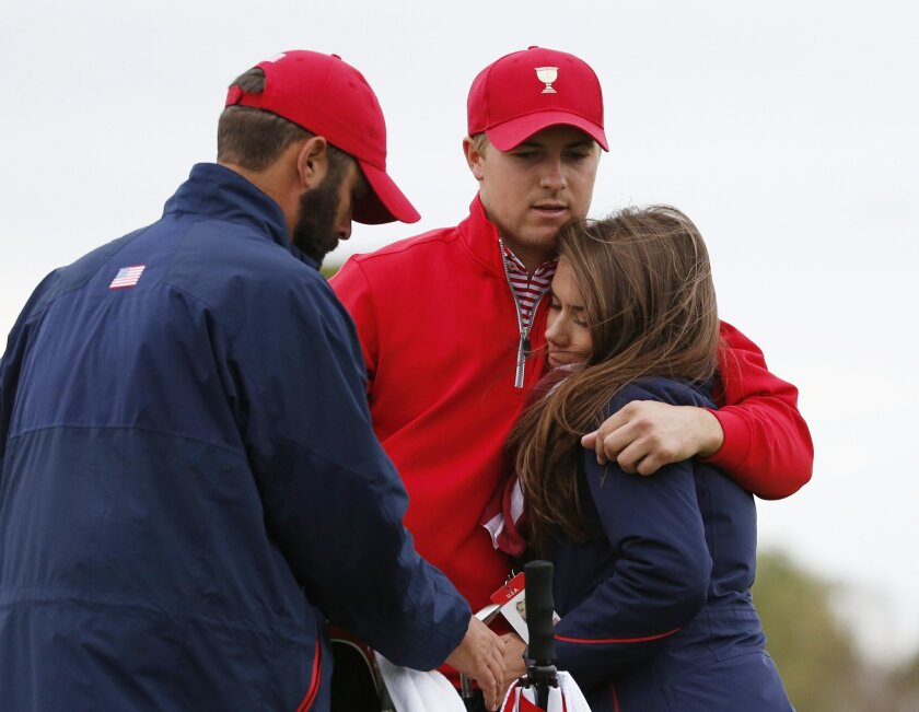 FILE - In this Oct. 11, 2015, file photo, United States' Jordan Spieth, center, is embraced by his girlfriend Annie Verret following his loss to International team player Marc Leishman of Australia in their singles match as Dustin Johnson, left, watches at the Presidents Cup golf tournament at the