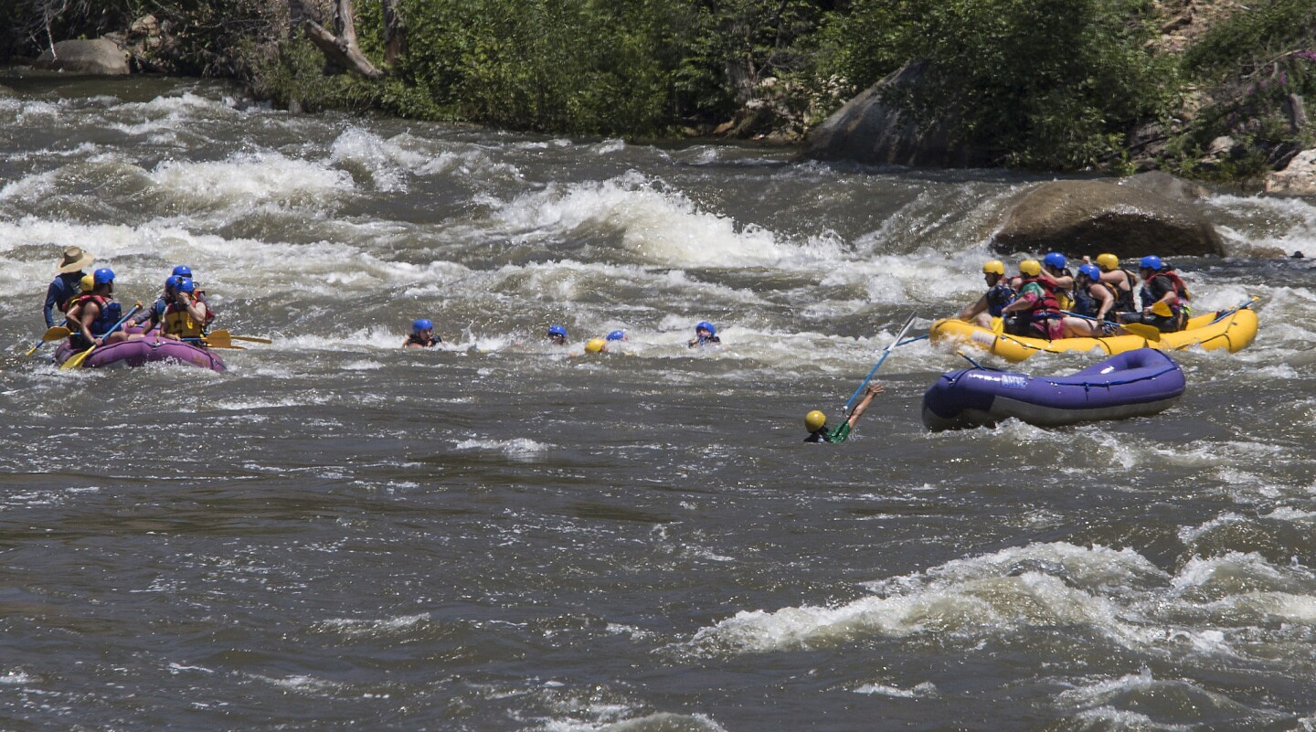 Rafters are dumped into the white water of the Ewing's rapids after their raft overturned on the Kern River in Kernville, Calif.