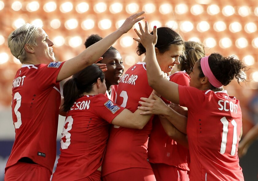 Canada's Christine Sinclair, center, is congratulated after scoring a goal against Trinidad & Tobago during the second half of a CONCACAF Olympic qualifying tournament soccer match Sunday, Feb. 14, 2016, in Houston. Canada won 6-0. (AP Photo/David J. Phillip)