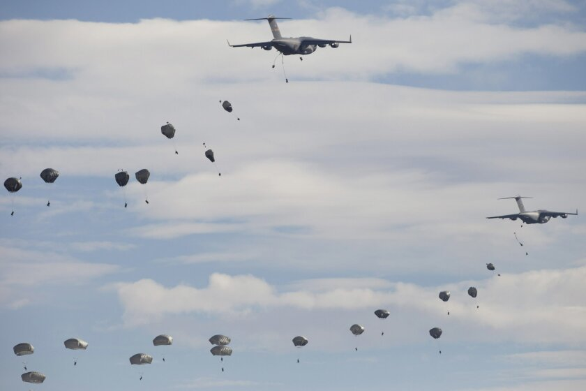 US paratroopers from the 82nd Airborne Division from Fort Bragg in North Carolina, jump of the US C-17 Globemaster aircraft during a NATO military demonstration in Zaragoza, Spain, Wednesday Nov. 4, 2015. NATO is putting on its most fearsome display of military might in over a decade with soldiers,