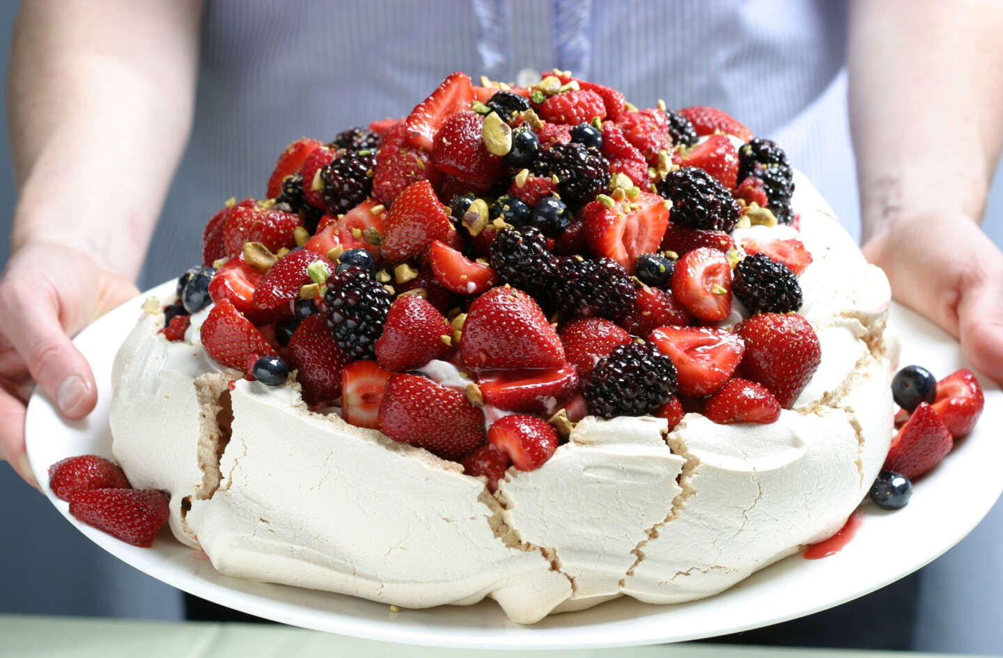 Sure to impress your guests. Recipe: Berry Pavlova with vanilla whipped cream and pistachios