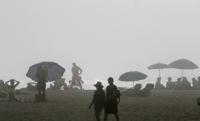Afternoon fog and cool temperatures limited the number of visitors to Huntington Beach on April 25, 2020. Beaches in neighboring Los Angeles County remain closed because of the coronavirus outbreak.