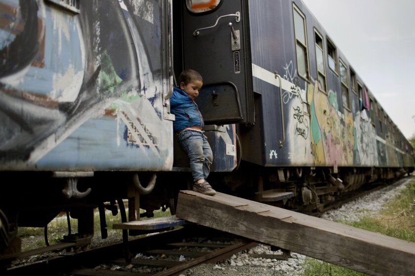 In this Sunday, May 8, 2016 photo, a child gets off a train that he lives in with his family in the sprawling refugee and migrant tent city of Idomeni, on Greece's northern border with Macedonia. (AP Photo/Petros Giannakouris)
