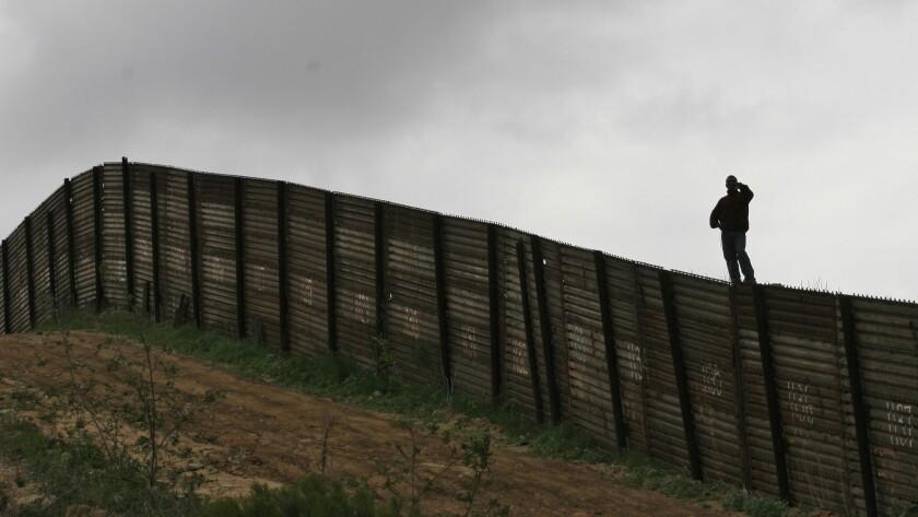 Hermin Ramos of Oaxaca, Mexico, looks over the U.S.-Mexico border fence near Smuggler's Gulch west o