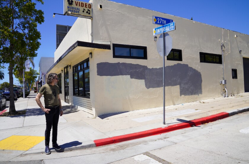 John Mireles points out mismatched paint on graffiti on an Imperial Avenue building in Logan Heights.