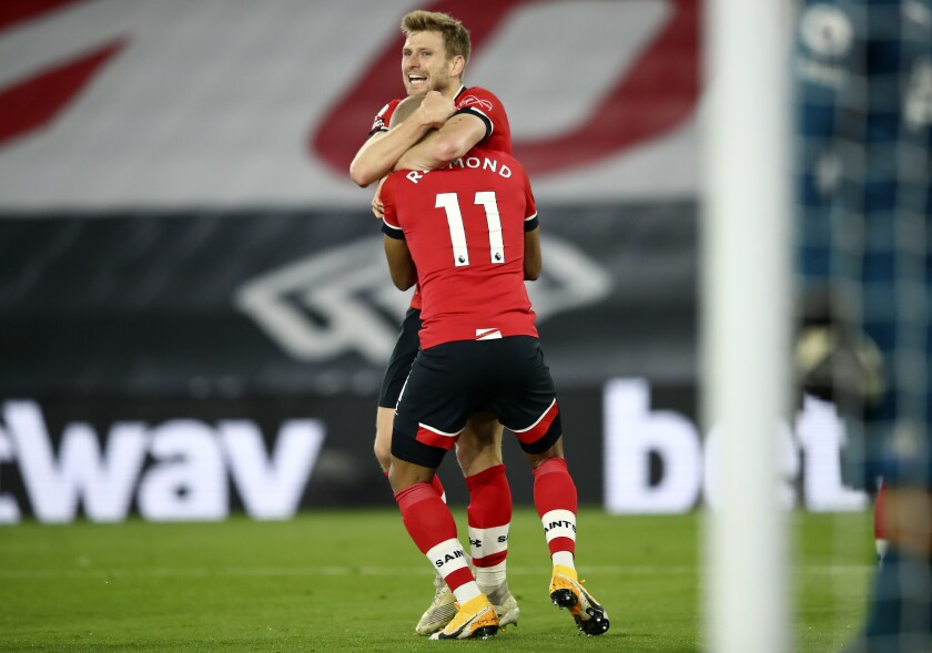 Southampton's scorer Stuart Armstrong, rear, and his teammate Southampton's Nathan Redmond, front, celebrate their side's second goal challenge for the ball during the English Premier League soccer match between Southampton and Newcastle United in Southampton, England, Friday, Nov. 6, 2020. (Michael Steele/Pool Photo via AP)