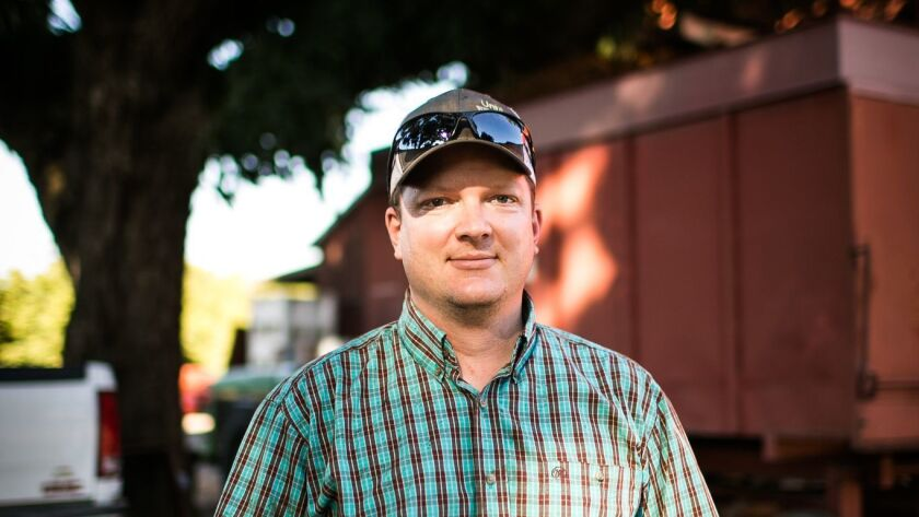 Walnut grower Jake Wenger poses for a portrait at his farm in Modesto, California, October15, 2018.