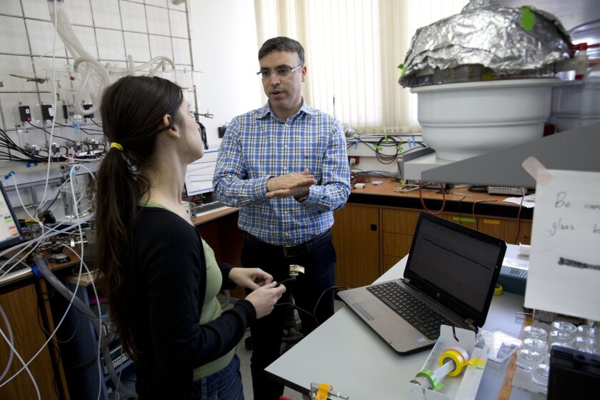In this Sunday, Feb. 14, 2016 photo, professor Hossam Haick talks to a researcher in his lab at Technion University in Haifa, Israel. Haick, whose breakthrough work in nanotechnology has garnered global accolades, says his success as an Arab citizen of Israel proves that education knows no boundaries and is key to improving his community's lot. (AP Photo/Dusan Vranic)