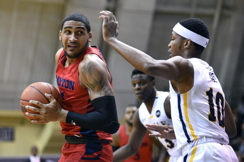 Dayton's Obi Toppin, left, works the ball past La Salle's Isiah Deas during the first half of an NCAA college basketball game, Thursday, Jan. 2, 2020, in Philadelphia. (AP Photo/Derik Hamilton)