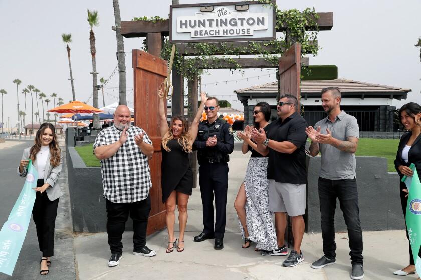 Prjkt chief executive Alicia Whitney raises the ceremonial scissors during a ceremony for the Huntington Beach House.
