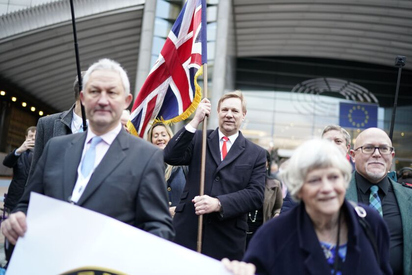 Jonathan Bullock, a British member of the European Parliament, holds the Union Jack flag as he leaves the European Parliament in Brussels