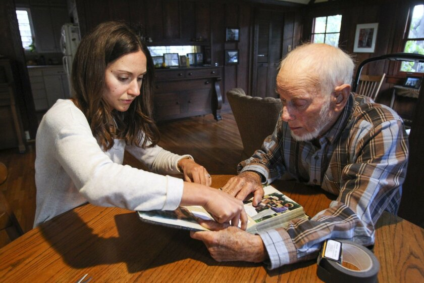 Becca Beville, a Companion Respite Program volunteer, helps Dale Laney, 83, who is diagnosed with early signs of dementia, fix his photo album with tape while in his home in San Diego on Wednesday.