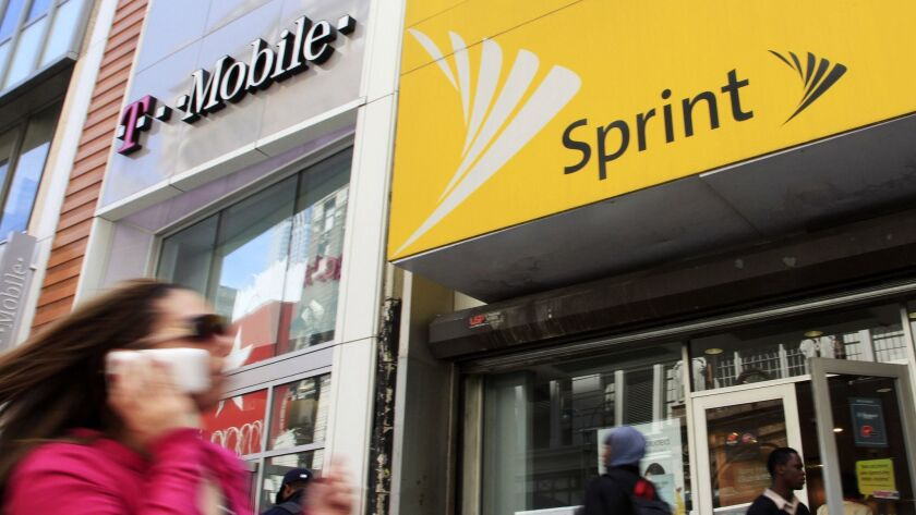 A woman using a cell phone walks past T-Mobile and Sprint stores in New York in 2010.