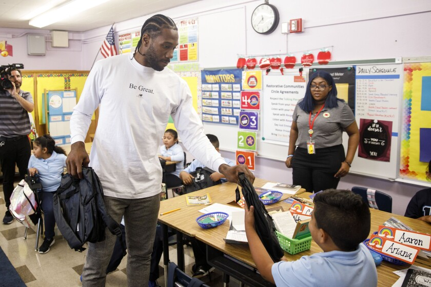 Clippers Kawhi Leonard gives backpacks away to students at One Hundred Seventh Street Elementary School on Tuesday in the Watts neighborhood of Los Angeles.