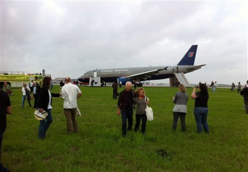 In this photo provided by Eric Long, people are evacuated from a United Airlines plane after making an emergency landing shortly after takeoff at Louis Armstrong New Orleans International Airport, Monday, April 4, 2011 in Kenner, La. The flight from New Orleans to San Francisco returned to the New Orleans airport within minutes of taking off Monday after rocking back and forth. Copilot Ronald Lee Young told an Associated Press reporter aboard Flight 497 that he landed on backup systems, with minimal steering and braking ability, after the plane lost all electronics. He said the plane, heavy with fuel, ran off the runway and blew a tire. (AP Photo/Eric Long) NO SALES
