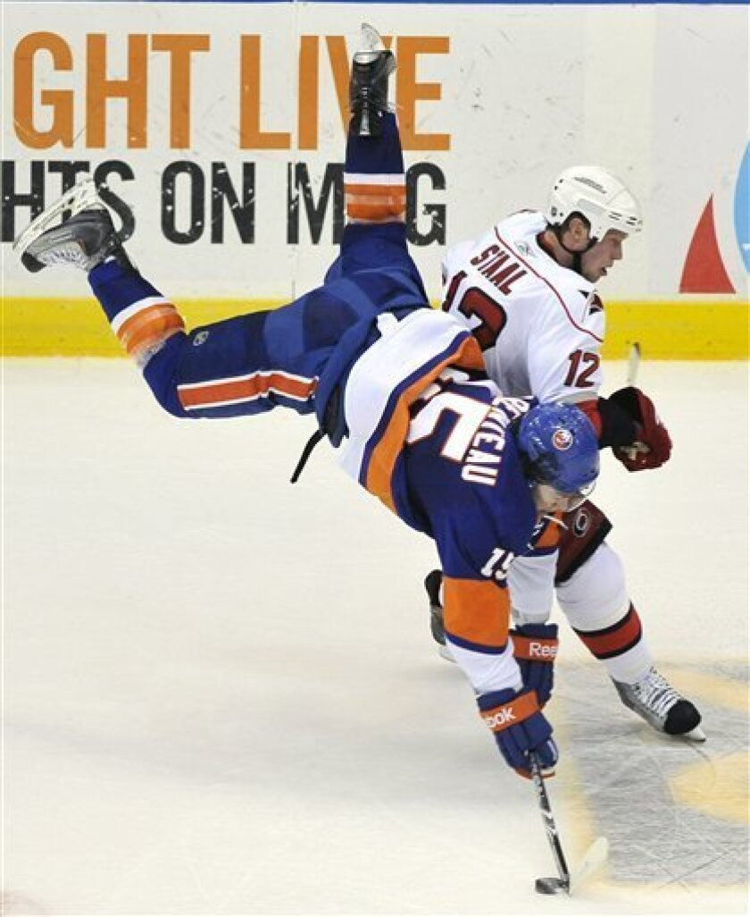 New York Islanders' P.A. Parenteau (15) goes airborne as he collides with Carolina Hurricanes center Eric Staal (12) during the second period of an NHL hockey game on Saturday, April 2, 2011, in Uniondale, N.Y. (AP Photo/Kathy Kmonicek)
