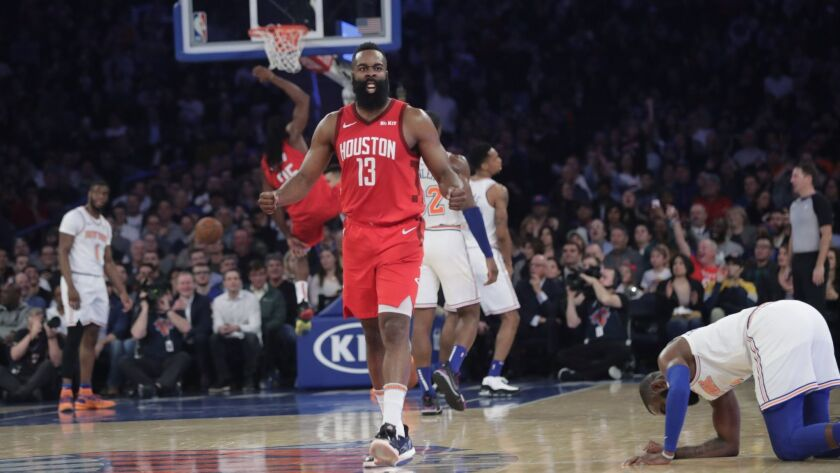 Houston Rockets' James Harden (13) reacts after teammate Kenneth Faried (35) dunked the ball during the second half of the team's game against the New York Knicks.