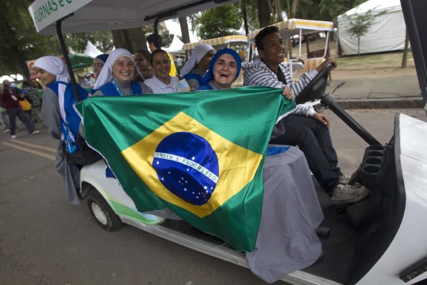 Nuns hold up a Brazilian flag as they ride through Quinta da Boa Vista park in Rio de Janeiro.
