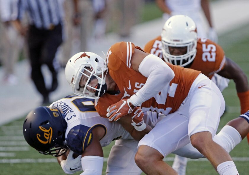 "Texas defensive back Dylan Haines, right, tackles California's Stephen Anderson, left, during the first half of an NCAA college football game, Saturday, Sept. 19, 2015, in Austin, Texas. Haines was called for ""targeting"" and ejected from the game. (AP Photo/Michael Thomas)"
