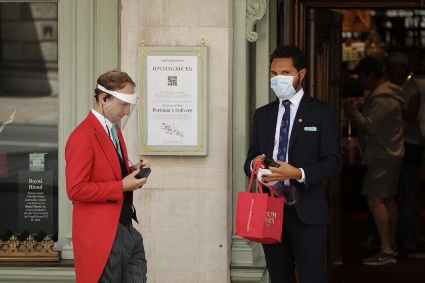 A doorman and colleague stand at the main entrance of the Fortnum & Mason department store in London. Parts of the store have reopened to customers.