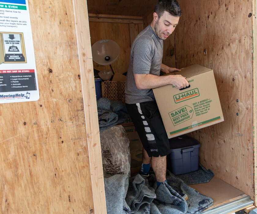Los Angeles Times reporter Liam Dillon moves boxes into his apartment in Palms in October.