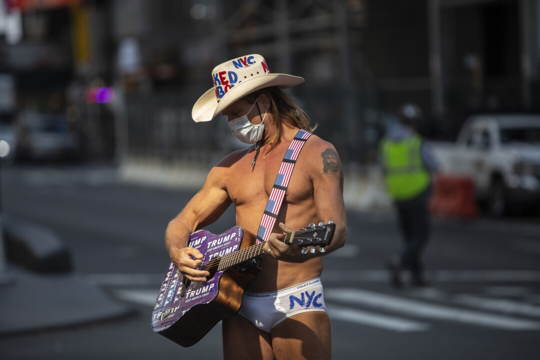 The Naked Cowboy plays his guitar in a mostly empty Times Square.