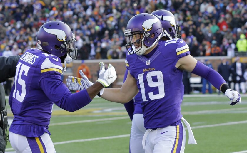 Minnesota Vikings wide receiver Adam Thielen (19) celebrates with teammate Greg Jennings, left, after catching a 44-yard touchdown pass during the second half of an NFL football game against the Chicago Bears, Sunday, Dec. 28, 2014, in Minneapolis. (AP Photo/Ann Heisenfelt)