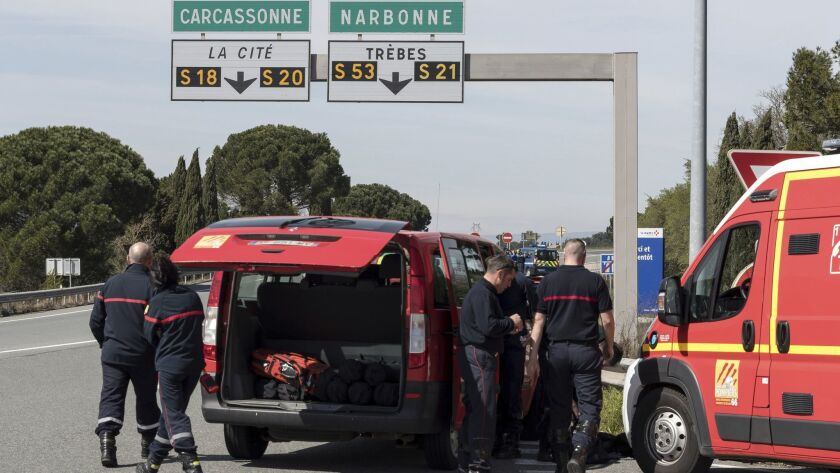French police and firefighters secure the entrance of Trebes, southern France, where an armed man to